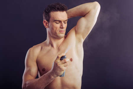 Portrait of handsome man using spray antiperspirant for his underarms, on a dark background Stock Photo