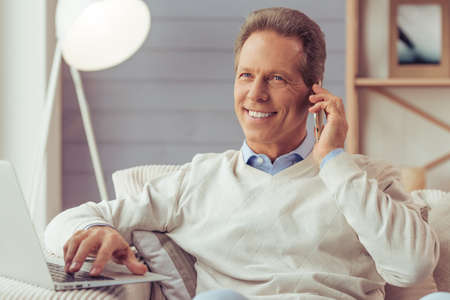 aged: Handsome middle aged businessman is talking on the mobile phone and smiling while working with a laptop at home Stock Photo