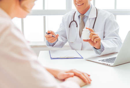 Cropped image of handsome doctor offering medicine to woman on consultation