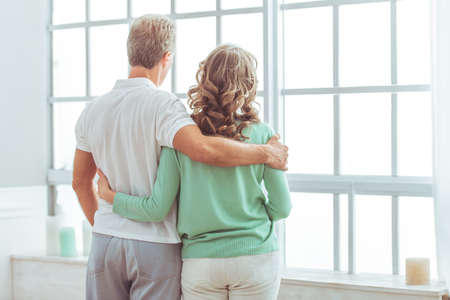 Back view of happy beautiful couple in casual clothes cuddling and looking out the window