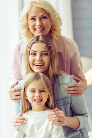 Portrait of three generations of happy beautiful women looking at camera, hugging and smiling Archivio Fotografico