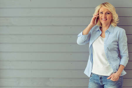 Beautiful mature woman in casual clothes is talking on the mobile phone, looking at camera and smiling, standing against gray background Foto de archivo