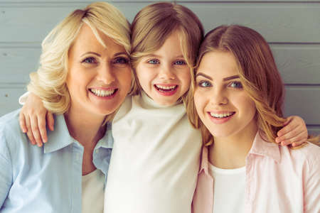 three generations of women: Portrait of three generations of beautiful women looking at camera, hugging and smiling, against grey background Stock Photo