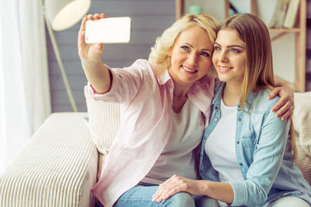 Portrait of beautiful mature mother and her daughter making a selfie using a smart phone and smiling, sitting on sofa at home