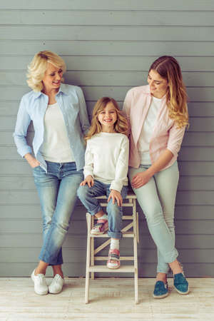 three generations: Three generations of women are smiling, standing against grey background. Little girl is looking at camera Stock Photo