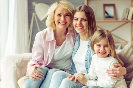 Granny, her daughter and granddaughter are looking at camera and smiling while sitting on sofa at home Stock Photo