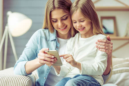 people sitting: Beautiful young mom and her little daughter are using a smartphone and smiling while sitting on sofa at home