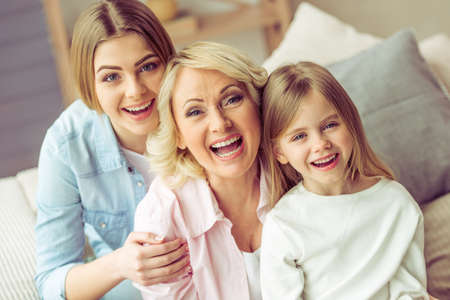 three generations of women: Portrait of three generations of happy beautiful women looking at camera, hugging and smiling Stock Photo