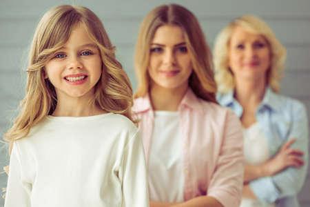 Trois générations de la famille regardent la caméra et souriant, debout, un par un. Jolie petite fille au premier plan Banque d'images