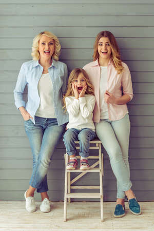 three generations of women: Three generations of beautiful women are looking at camera, showing surprise and smiling, standing against grey background Stock Photo