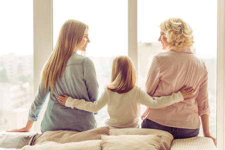 three generations of women: Back view of three generations of beautiful women sitting on sofa against window