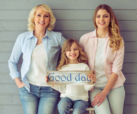 three generations of women: Three generations of women are looking at camera and smiling, standing against grey background. Little girl with a wooden plate Good day