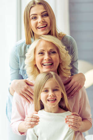 Portrait of three generations of happy beautiful women looking at camera, hugging and smiling Фото со стока