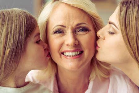 abuela: Hermosa abuela est� mirando la c�mara y sonriendo mientras que su hija y su nieta est�n besando su