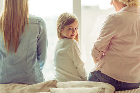 pretty little girl: Back view of three generations of beautiful women sitting on sofa against window. Little girl looking at camera and smiling Stock Photo