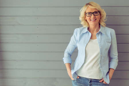 La bella donna matura in vestiti casuali e gli occhiali sta esaminando la macchina fotografica e sta sorridendo, stante contro fondo grigio