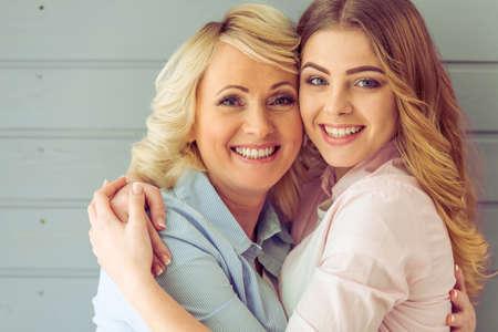Retrato de la madre hermosa madura y su hija abrazados, mirando a la cámara y sonriendo, sobre fondo gris