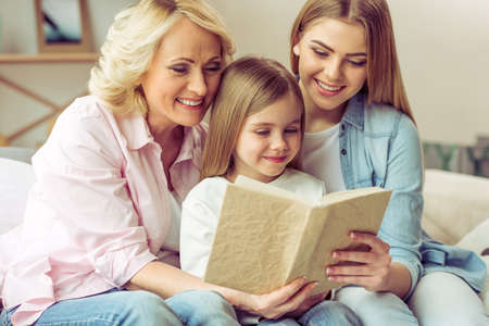 Granny, her daughter and granddaughter are reading a book and smiling while sitting on sofa at home