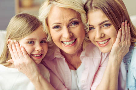 Portrait of three generations of happy beautiful women looking at camera, hugging and smiling Imagens