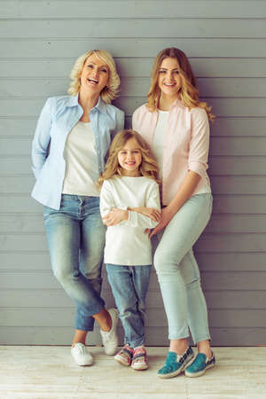 Three generations of beautiful women are looking at camera and smiling, standing against grey background