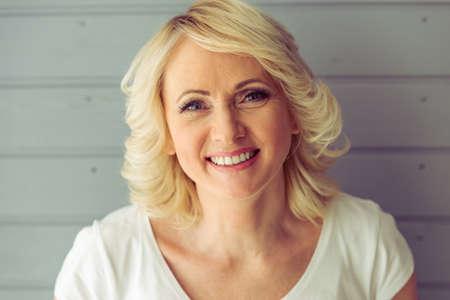 Portrait der schönen reifen Frau, die Kamera und das Lächeln, vor grauem Hintergrund