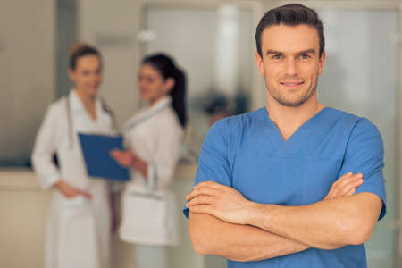 Joven y apuesto doctor está mirando la cámara y sonriente, de pie con los brazos cruzados en el pasillo del hospital Foto de archivo - 55359464