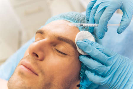 medical injection: Handsome young man is getting an injection in face, lying with closed eyes, close-up Stock Photo