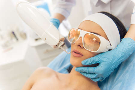 undertaking: Beautiful young woman is getting face skin treatment. Doctor in medical gloves is undertaking the procedure using a modern equipment