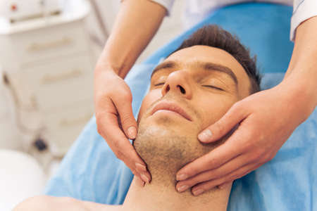 Portrait of handsome young man getting a face massage, lying with closed eyes