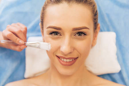 cosmetician: Top view of beautiful young woman getting face skin treatment, looking at camera and smiling. Cosmetician is using a brush Stock Photo