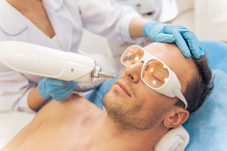 undertaking: Handsome man is getting face skin treatment. Doctor in medical gloves is undertaking the procedure using a modern equipment