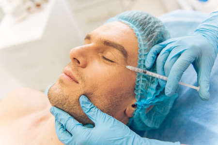 inyeccion: Apuesto joven está recibiendo una inyección en la cara, acostado con los ojos cerrados Foto de archivo