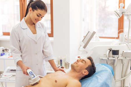 health professional: Handsome man is getting skin treatment. Female doctor is undertaking the procedure using a modern equipment Stock Photo