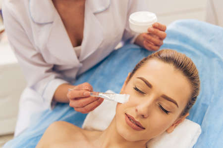 cosmetician: Beautiful young woman is getting face skin treatment. Cosmetician is holding a bottle of cream and using a brush