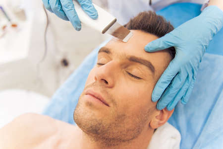 Portrait of handsome man getting face skin treatment. Doctor is undertaking the procedure using a modern equipment Stock Photo
