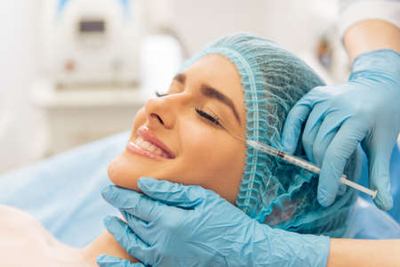Beautiful young woman is getting an injection in her face and smiling, lying with closed eyes