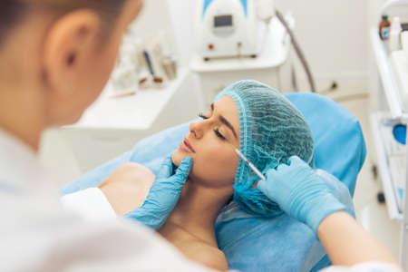 아름 다운 젊은 여자는 성형 수술에 닫힌 된 눈으로 거짓말 그녀의 얼굴에 주입을 받고있다