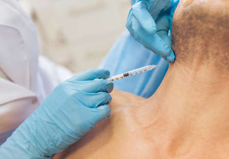 Doctor in medical gloves is giving an injection in man neck, close-up Stock fotó
