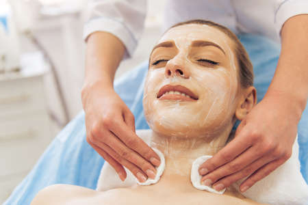 undertaking: Beautiful young woman getting face skin treatment, lying with cream on her face. Doctor is undertaking the procedure using sponges