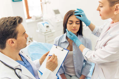 Beautiful young woman is sitting with closed eyes in doctors office, two doctors are examining her face and making notes Stock Photo
