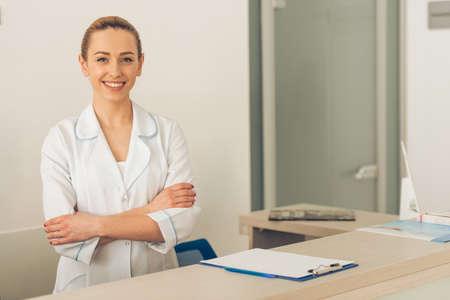 美しい若い女性医師はカメラ目線や笑顔、クリニックの待合室で立っています。