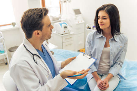 Handsome doctor is talking with young female patient and making notes while sitting in his office Stockfoto