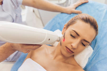 undertaking: Beautiful woman is getting face skin treatment. Doctor is undertaking the procedure using a modern equipment