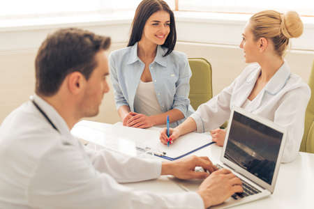 Handsome doctor is using a laptop. In the background female doctor is giving a consultation to woman