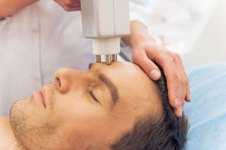 undertaking: Handsome man is getting face skin treatment. Doctor is undertaking the procedure using a modern equipment, close-up