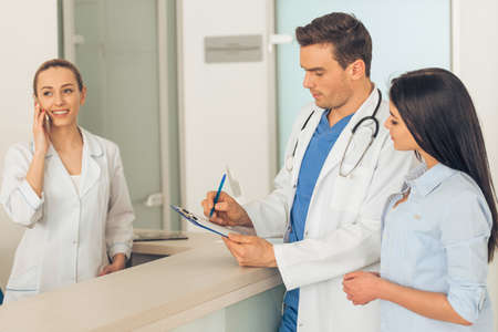 Handsome young doctor is holding a folder and talking with a beautiful female patient, standing in waiting room of the clinic