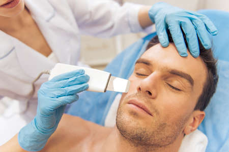Handsome man is getting face skin treatment. Doctor in medical gloves is undertaking the procedure using a modern equipment