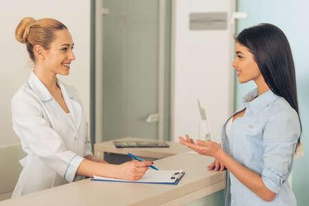 medico: Hermosa mujer joven médico está hablando con el paciente y sonriente, de pie en la sala de espera de la clínica Foto de archivo