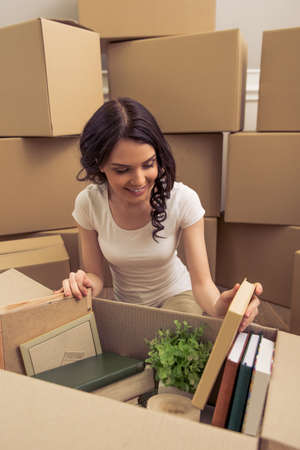 'young things': Attractive young woman is moving, smiling and looking through things while packing, sitting among cardboard boxes