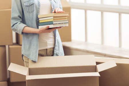 Cropped image of attractive young woman moving, packing books in cardboard box, looking at camera and smiling Foto de archivo